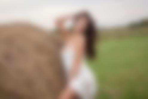 Обои Модель Niemira с длинными волосами в приспущенном белом платье стоит у стога с сеном в поле