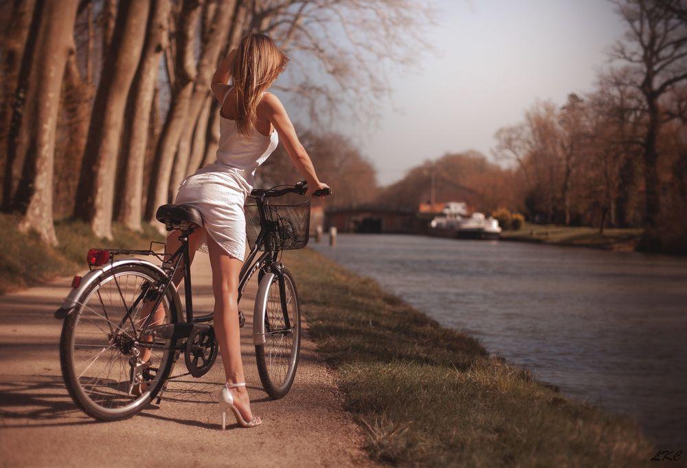 Обои для рабочего стола Девушка в коротком белом платье на велосипеде стоит на дорожке на бергу реки