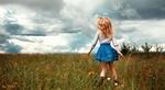 Обои Девочка - блондинка в голубой юбочке и кофте бежит по полю, фотограф Aleksandr Suhar