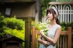 Обои Азиатка с букетом белых роз стоит возле деревянной калитки