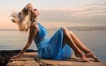 Обои Блондинка в синем платье сидит на каменистом берегу морского залива, на фоне неба с облаками
