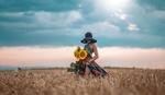 Обои Девушка в шляпе с подсолнухами в руках стоит в поле