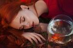 Обои Рыжеволосая девушка с закрытыми глазами лежит перед аквариумом с рыбкой. Фотограф Марина Жаринова