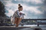 Обои Симпатичная девушка сидит на корточках на набережной реки