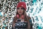 Обои Девушка в зимней шапке и наушниках стоит на фоне бликов, фотограф Ali Pazani