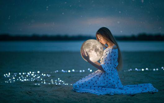 Молодая девушка в красивом платье с луной в руках на песке