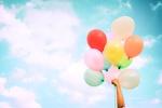 Обои Женская рука с разноцветными воздушными шариками на фоне неба