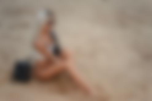 Обои Девушка-блондинка сидит на песке