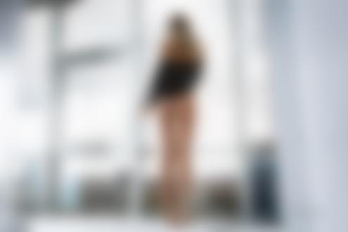 Обои Стройная блондинка в приспущенной кожанке и в трусиках стоит спиной к камере у окна с видом на город, фотограф Артем Савинков