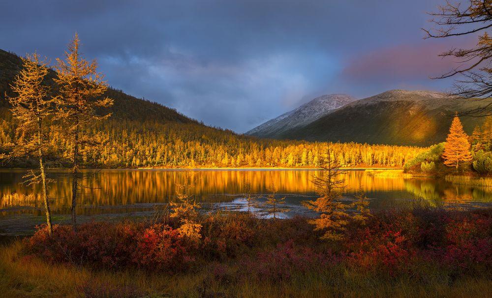 Обои для рабочего стола Тихое озеро в лучах осеннего солнца на фоне гор под пасмурным небом, фотограф raufz