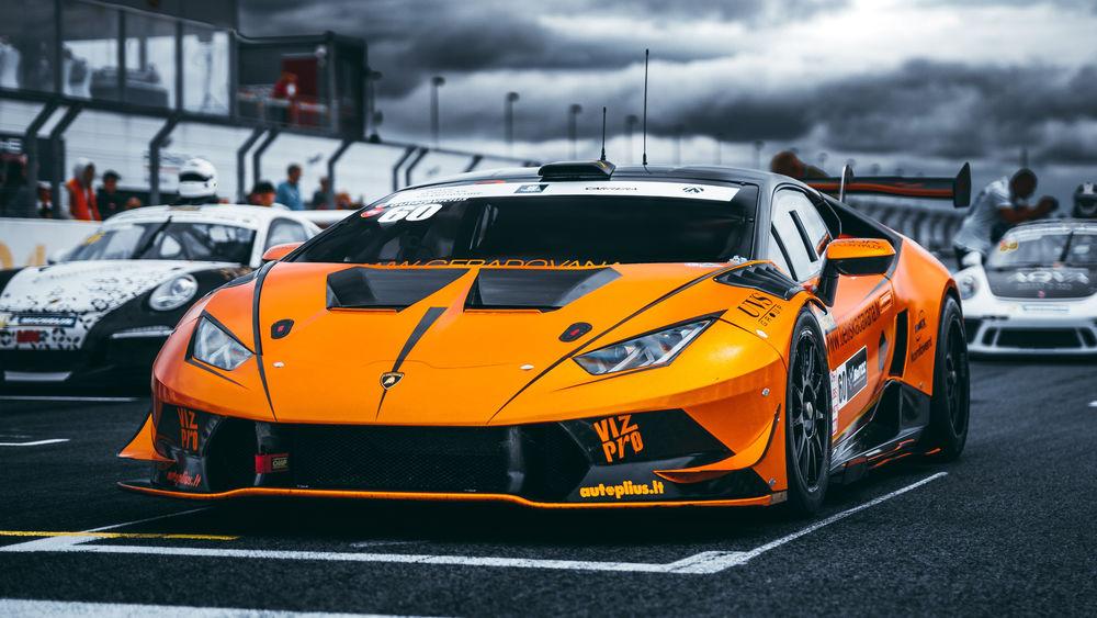 Обои для рабочего стола Оранжево-черный Lamborghini Aventador на старте заезда