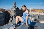 Обои Девушка в голубом платье сидит на крыше дома