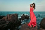 Обои Девушка в алом платье стоит на фоне моря