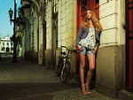 Обои Длинноволосая девушка в джинсовых шортах стоит у стены здания на городской улице