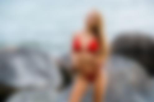 Обои Девушка в красном купальнике стоит на фоне камней и моря