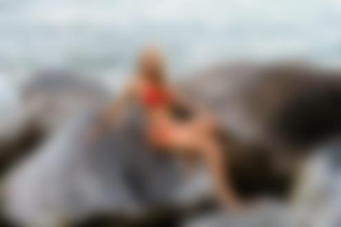 Обои Девушка в красном купальнике сидит на камнях