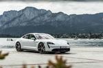 Обои Белый Porsche Taycan Turbo S 2019 стоит на побережье с видом на поселок у подножья скал