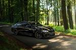 Обои Черный BMW M5 F90 в тюнинге от автоателье Manhart, стоит на асфальтированной дороге в лесу