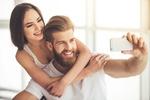 Обои Девушка обнимает парня, который держит в руке телефон и им фотографирует