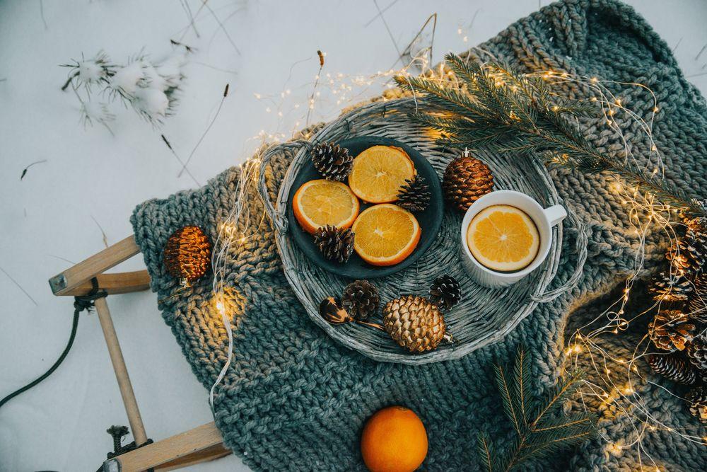 Обои для рабочего стола Апельсины, шишки и чашка с чаем стоит на вязанной вещи с еловыми ветками и гирляндой, by Anita Austvika