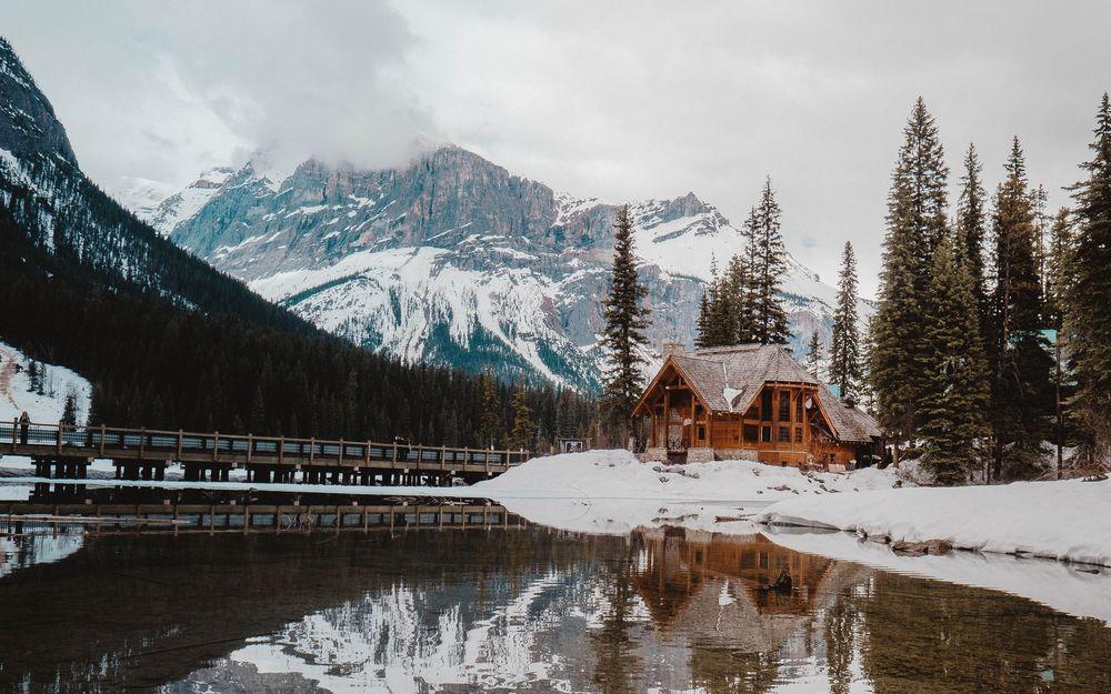 Обои для рабочего стола Люди гуляют по мосту, который ведет к дому у небольшого горного озера, by Devon Hawkins
