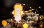 Обои Пряник новогодний в виде ангелочка на пеньке с еловыми веточками на размытом фоне. Фотограф Кукота Екатерина