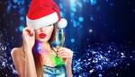Обои Девушка в новогодней шапке с бокалом шампанского стоит на синем фоне с блестками, авторВСубботина Анна