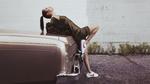 Обои Фотомодель Белла Хадид стоит у автомобиля в кроссовках, прогнувшись к капоту
