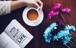 Обои Женская рука держит чашку чая, стоящую на столе, рядом лежит книга и цветы