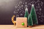 Обои Три новогодние елки на фоне расписного фона и подарок с шариком и за ним игрушечный олень
