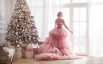 Обои Блондинка в розовом бальном платье стоит спиной у окна рядом с нарядной новогодней елкой, автор еlenachhil