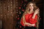 Обои Длинноволосая блондинка в красной кофточке стоит на фоне новогодней елки в комнате