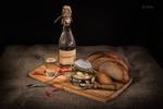 Обои На столе на разделочной доске стоят бутылка и стакан с самогоном, рядом лежат хлеб, перец и открытая консервная банка с рыбой, фотограф Вера Калинкина