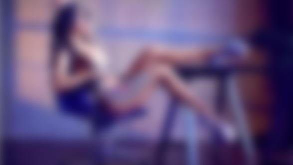Обои Девушка в туфлях на платформе и ремнях сидит в кресле положив одну ногу на стол