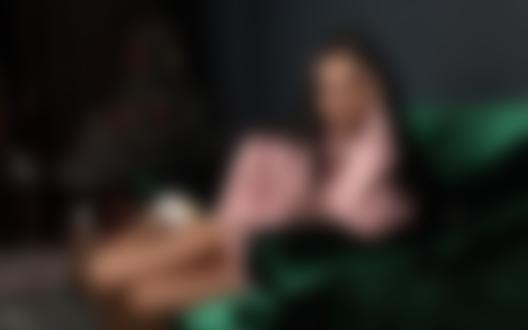Обои Девушка в розовом свитере сидит на диване в комнате с новогодней елкой