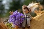 Обои Фигурка игрушечного мальчика в шляпе на фоне цветов хепатики, by Ingrid