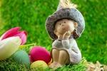 Обои Игрушечная фигурка девочки в шляпе сидящая на траве на фоне пасхальных яиц и белого и розового тюльпанов, by Ingrid