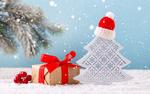 Обои Декоративная елка с шапкой на ней и подарок рядом на снегу