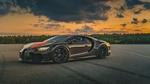 Обои Черный с оранжевыми полосами Bugatti Chiron Super Sport 2019 стоит на треке под вечерним небом