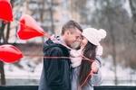 Обои Парень обнимает девушку в белой вязаной шапке, держащую воздушные красные шары в виде сердечек на размытом фоне, by StockSnap