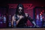 Обои Мужчина в очках с биомеханической рукой сидит в баре курит и пьет алкоголь в неоновой обстановке