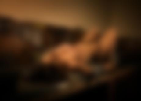 Обои для рабочего стола Девушка в приспущенных черных трусиках топлес лежит на рабочем столе в мастерской