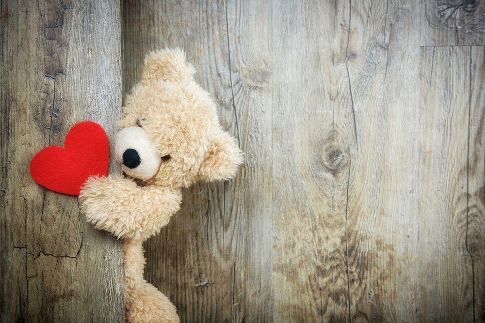 Обои для рабочего стола Плюшевый медвежонок держит сердечко лапой на деревянной поверхности, byBruno