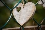 Обои Деревянное сердечко на шнурке лежит на сетчатом заборе