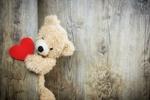 Обои Плюшевый медвежонок держит сердечко лапой на деревянной поверхности, byBruno