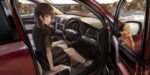 Обои Девочка сидит в авто, а в окошке окрытой дверцы-рыжий котик