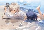 Обои Девочка с фотоаппаратом лежит у моря