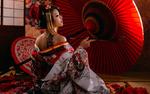 Обои Девушка-азиатка в кимоно с тату на спине и курительной трубкой в руке сидит на полу рядом с зонтом