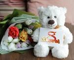 Обои Игрушечный мишка с открыткой 8 марта сидит рядом с букетом тюльпанов