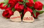 Обои Букет красных тюльпанов лежит на столе, рядом 2 сердечка с надписями frauentag и 08. 03